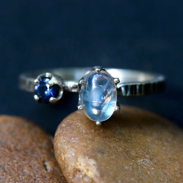Oval moonstone ring in silver prongs setting and blue sapphire on the side with sterling silver texture band - Metal Studio Jewelry