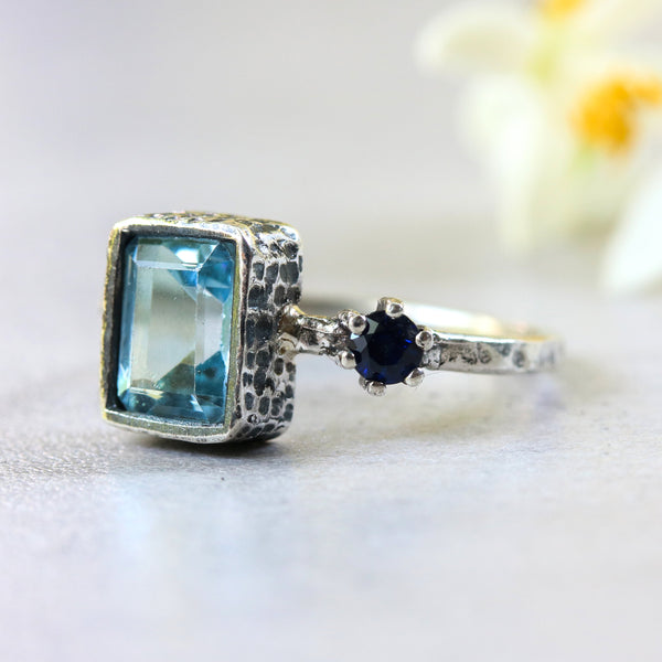 Rectangle blue topaz ring in silver bezel setting with tiny blue sapphire