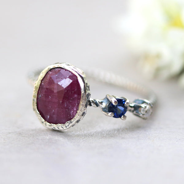 Oval faceted ruby ring in silver bezel setting with tiny blue sapphire and labradorite on sterling silver twist design band - Metal Studio Jewelry