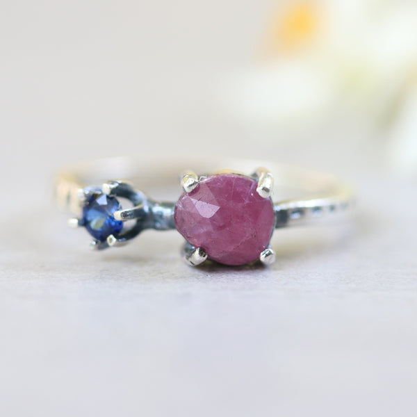 Faceted ruby ring in silver prongs setting and tiny round blue sapphire