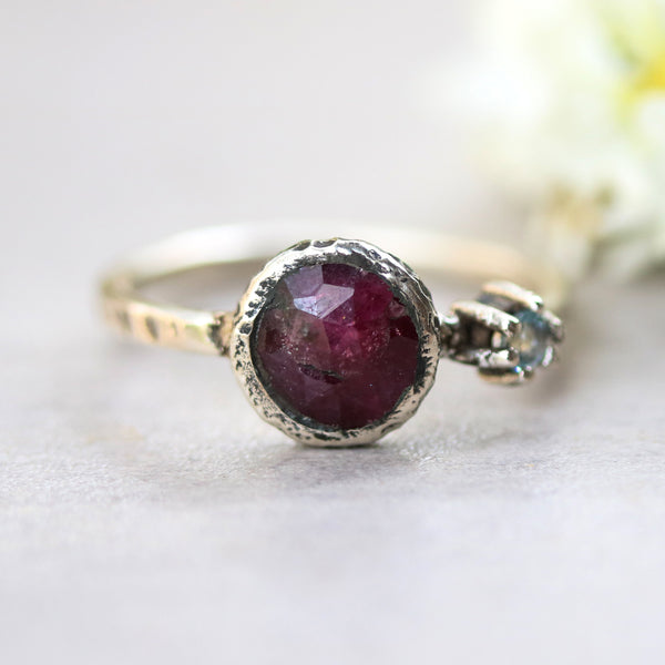 Round ruby ring in bezel setting with round blue topaz on sterling silver oxidized texture band - Metal Studio Jewelry