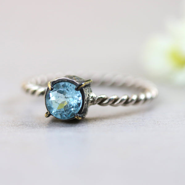 Round faceted blue topaz ring in silver bezel and brass prongs setting with sterling silver twist design band - Metal Studio Jewelry