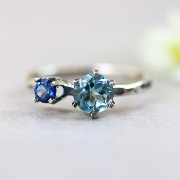 Round blue topaz ring in silver prongs setting and tiny blue sapphire on the side - Metal Studio Jewelry