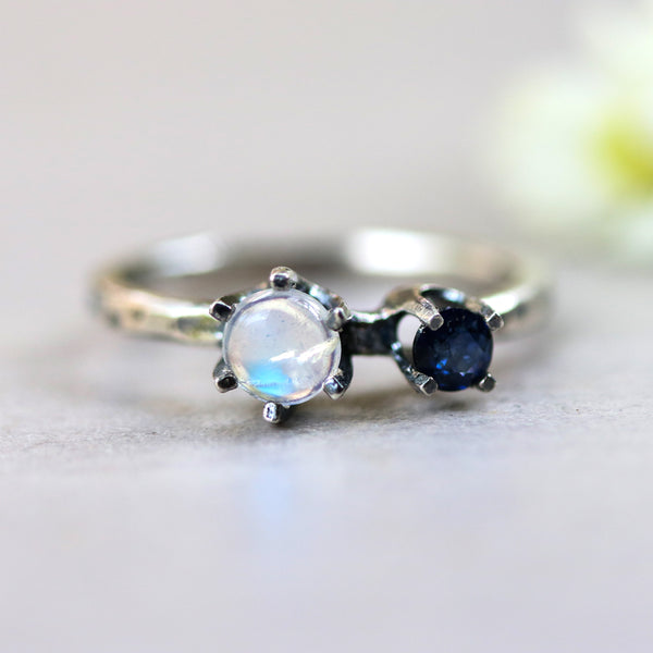 Round cabochon moonstone ring in silver prongs setting and tiny blue sapphire on the side with sterling silver hammer texture band - Metal Studio Jewelry