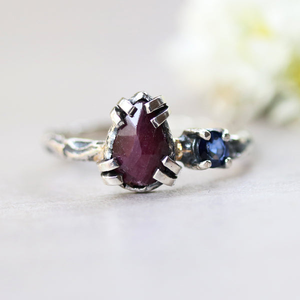 Tiny teardrop ruby ring in double prongs setting and tiny blue sapphire with sterling silver oxidized hard texture band - Metal Studio Jewelry