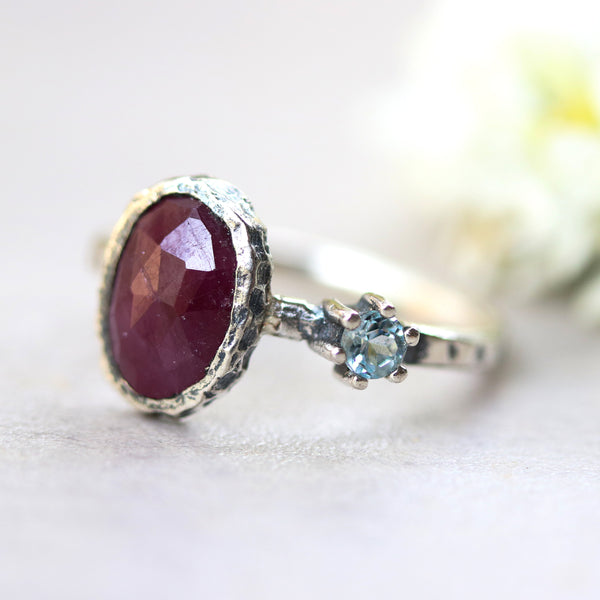 Oval Ruby ring in bezel setting with round blue topaz on sterling silver oxidized texture band - Metal Studio Jewelry