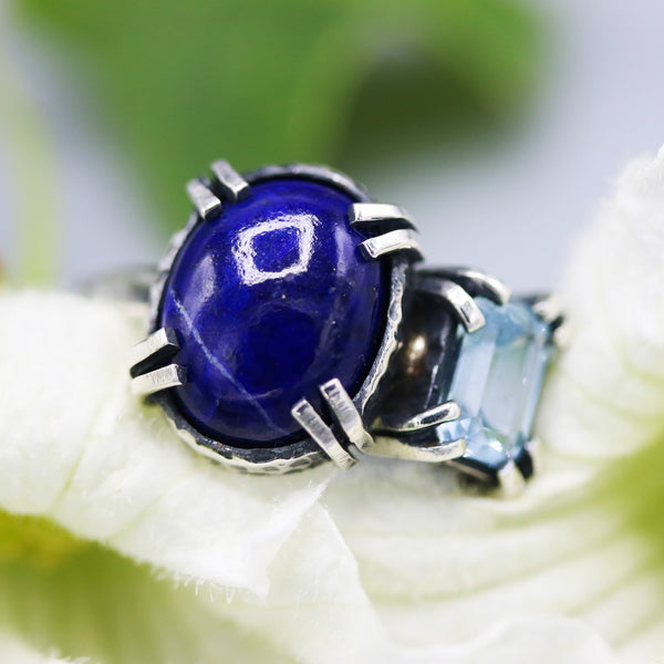 Oval faceted Lapis lazuli ring in silver bezel and double prongs setting with blue topaz on the side - Metal Studio Jewelry