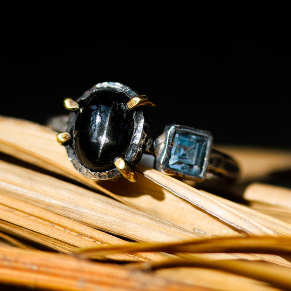 Black star diopside cabochon ring in silver bezel and brass prongs setting with blue topaz on the side - Metal Studio Jewelry