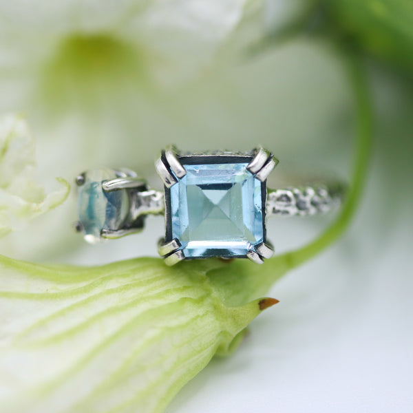 Princess cut Swiss blue topaz ring in silver bezel and double prongs setting with tiny moonstone - Metal Studio Jewelry