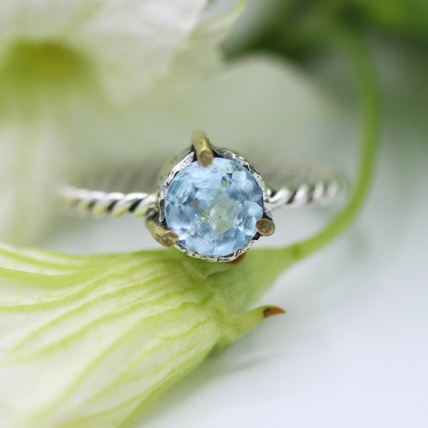 Round faceted Swiss blue topaz ring in silver bezel and brass prongs setting on sterling silver twist design band - Metal Studio Jewelry