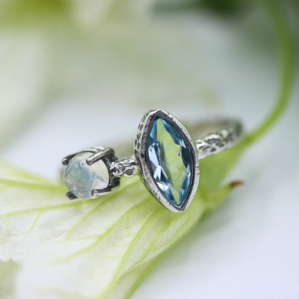 Marquis faceted blue topaz ring in silver bezel setting and round moonstone on the side with sterling silver hard texture band - Metal Studio Jewelry