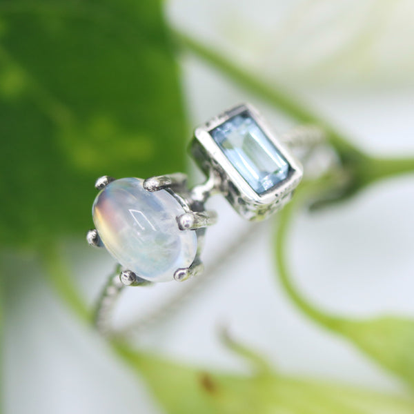 Oval moonstone ring in silver prongs setting and tiny blue topaz on the side - Metal Studio Jewelry
