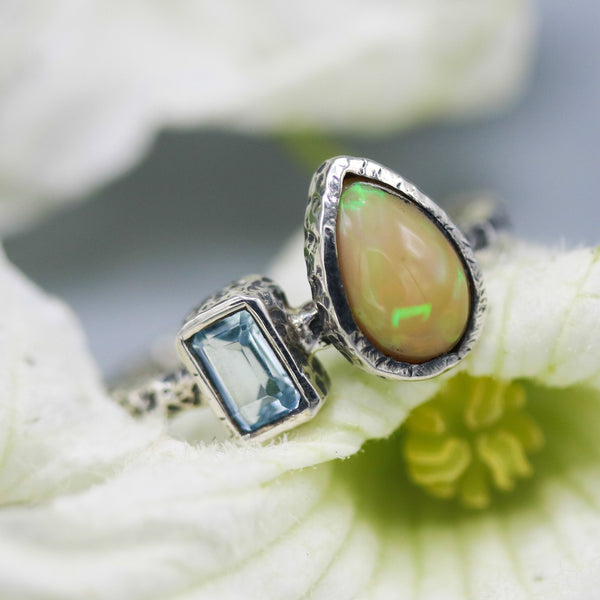 Teardrop fire opal ring and tiny blue topaz on the side set in bezel setting with sterling silver oxidized textured band - Metal Studio Jewelry