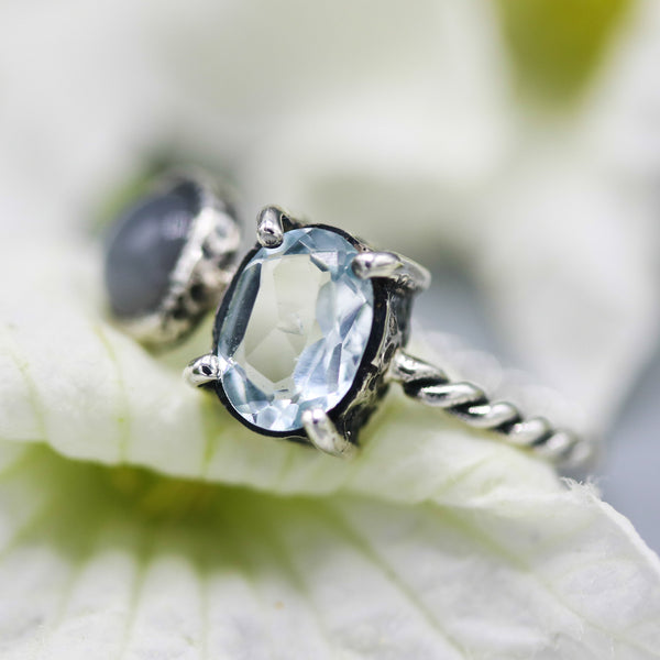 Oval faceted blue topaz ring in silver prongs setting and tiny moonstone on the side with sterling silver twist design band - Metal Studio Jewelry