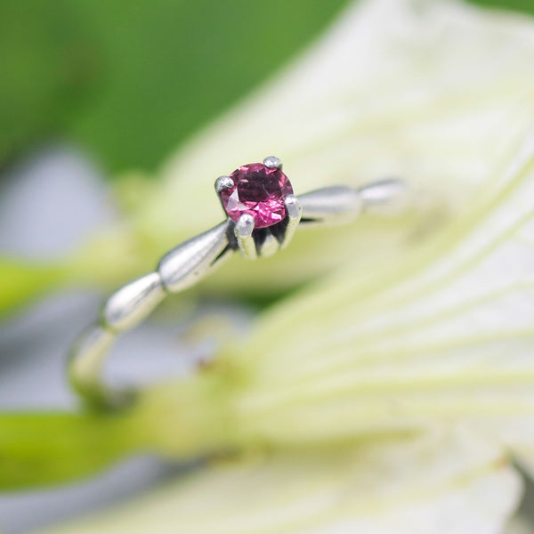 Dainty silver band with faceted round pink tourmaline gemstone in prongs setting