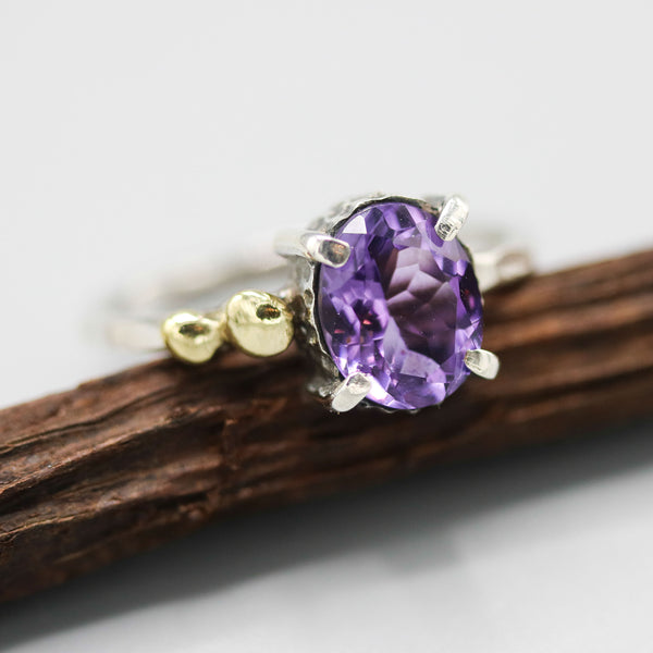 Oval faceted Amethyst ring in silver bezel and prongs setting and brass beads on the side with sterling silver texture band - Metal Studio Jewelry