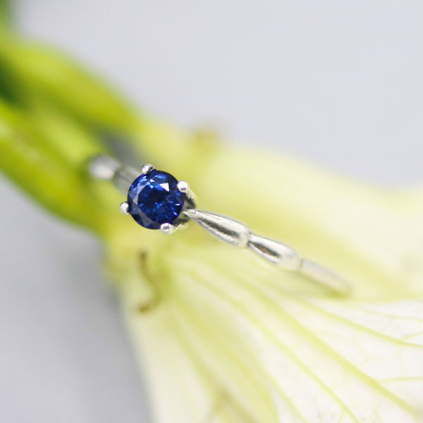 Dainty silver band with round faceted blue sapphire gemstone in prongs setting
