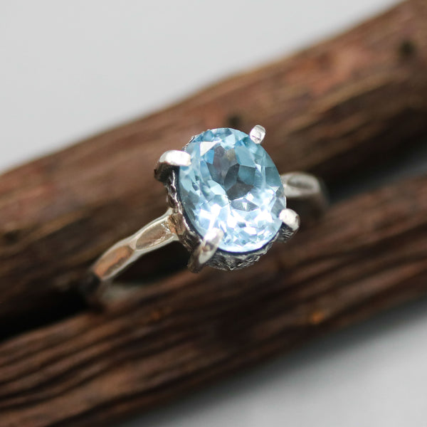 Oval Swiss blue topaz ring in silver bezel and prongs setting with sterling silver hammer texture band - Metal Studio Jewelry