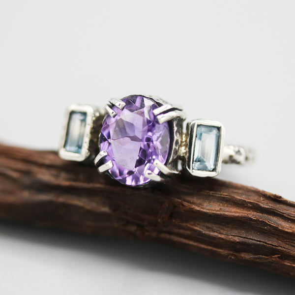 Oval Amethyst ring in silver bezel and double prongs setting with blue topaz on the side set on sterling silver texture oxidized band - Metal Studio Jewelry