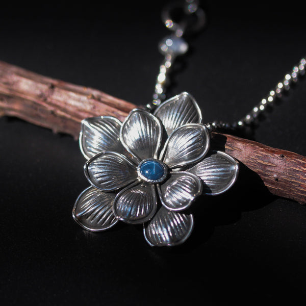 Blue star sapphire in silver flower necklace with moonstone on the side