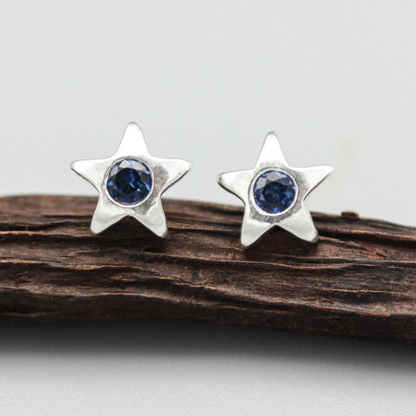 Star shape stud earrings with faceted blue sapphire in bezel setting with sterling silver post and backing