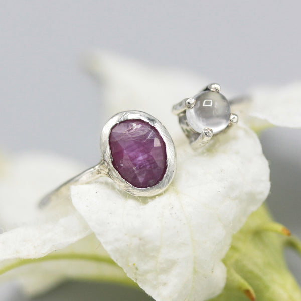 Oval faceted Ruby ring and tiny moonstone side set gems in bezel and prongs setting with sterling silver band