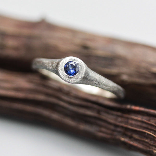 Sterling silver brush texture oxidized ring with tiny round faceted blue sapphire in silver bazel setting