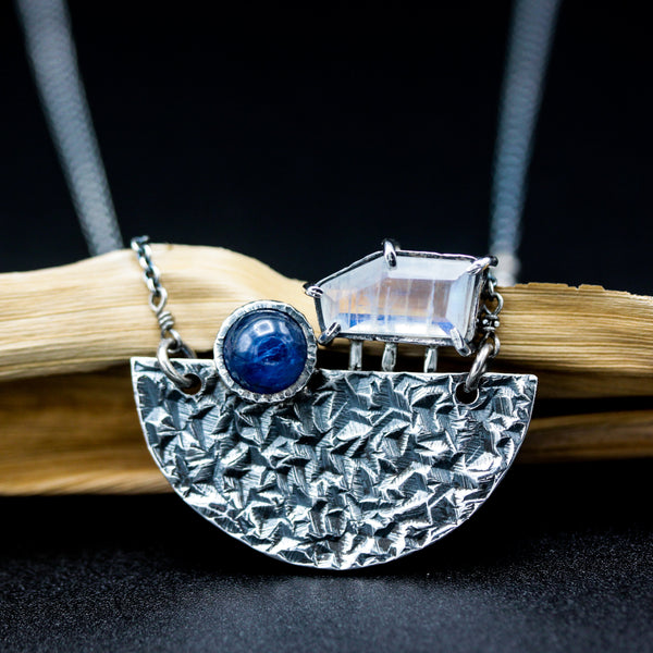 Faceted moonstone pendant necklace and blue kyanite in silver bezel setting set in silver textured fan shape