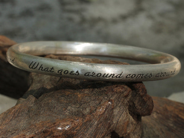 "Textured silver bangle with text ""what goes around comes around"""