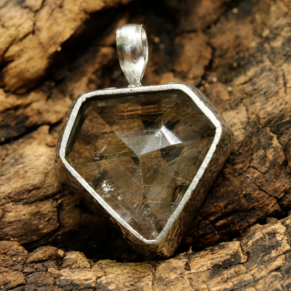 Rutilited quartz in shield faceted pendant in silver bezel setting with polished silver accent prongs