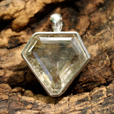 Rutilated quartz  in shield faceted pendant in silver bezel setting with polished silver accent prongs