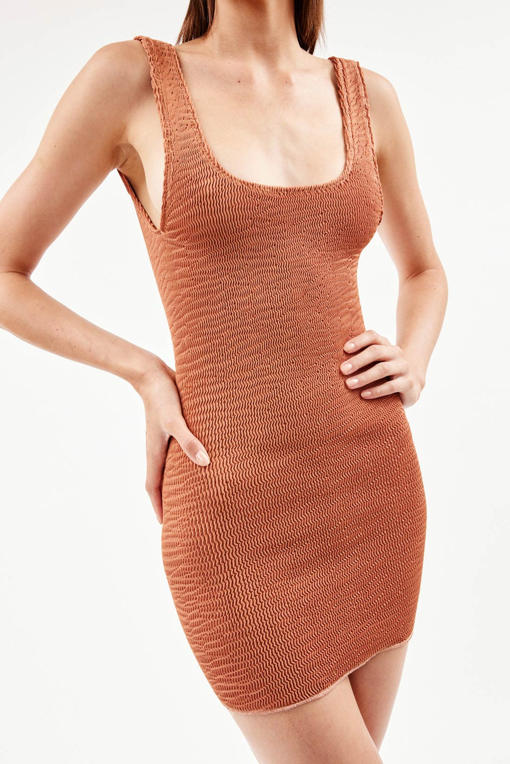 Model wears bronze mini dress featuring low back, over the shoulder straps, scoop neck, sustainable crinkle fabrication