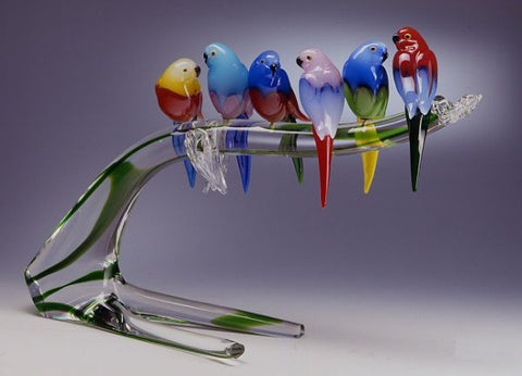Colourful Murano glass garden birds on a low branch