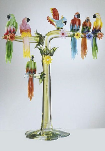 Seven colourful Murano glass parrots on a high branch
