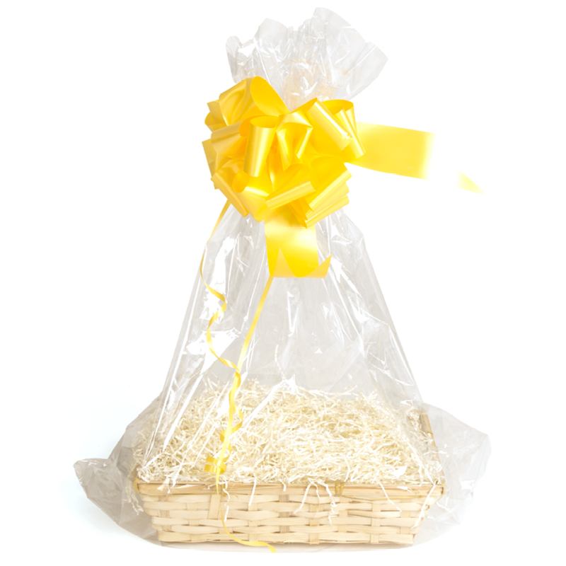 A basket with cream shred wrapped in a cellophane bag with a yellow bow