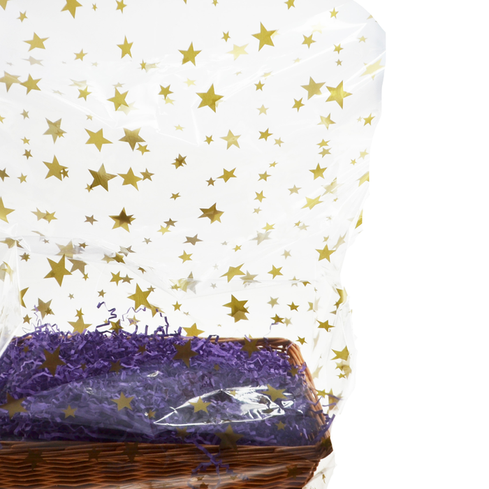 A basket with purple shred wrapped in a cellophane bag with a stars pattern