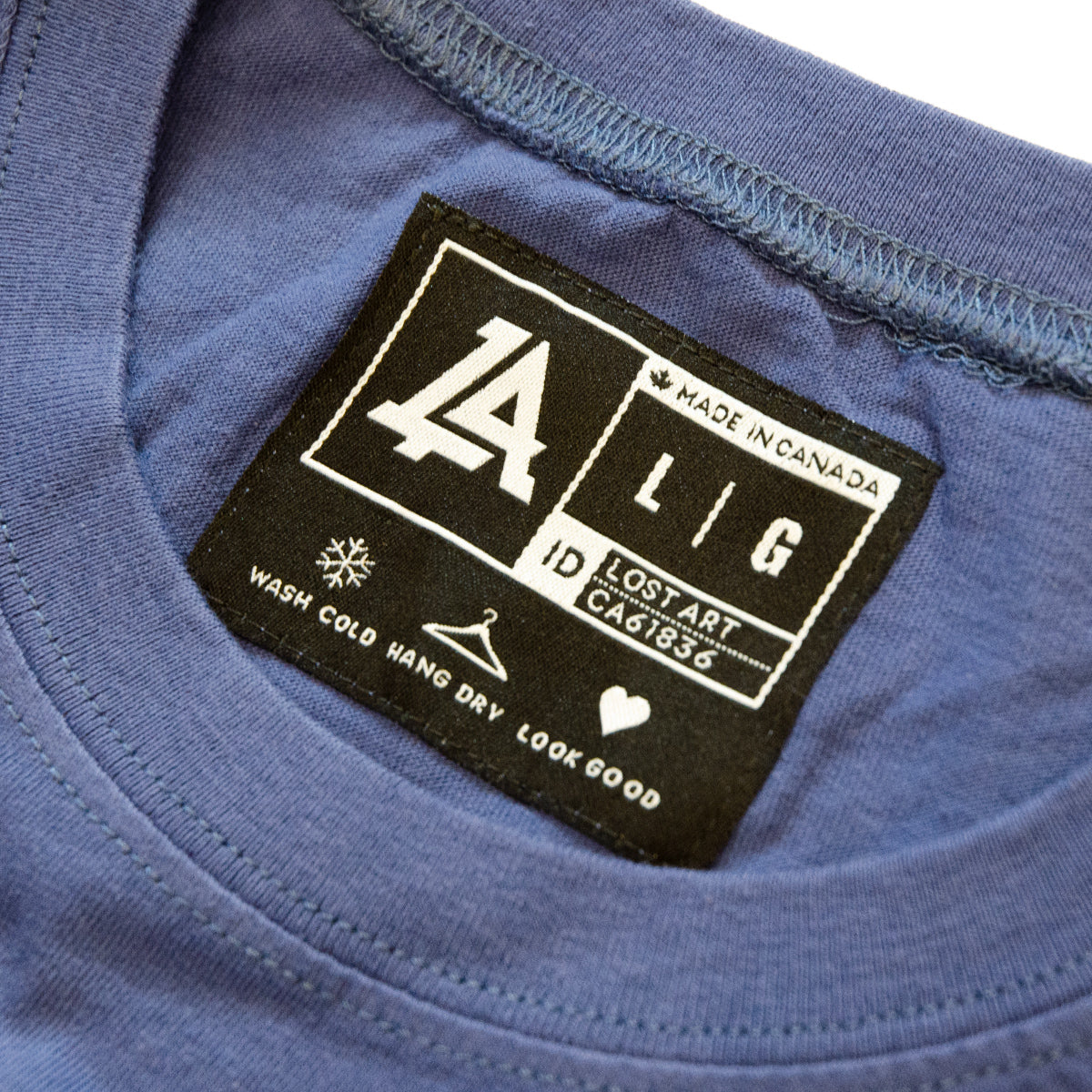 Lost Art Canada - white on royal blue lost art icon logo tee inside tag view