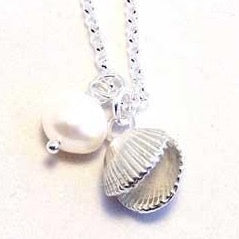 This is a unique solid silver double sided cockle shell is formed in thick silver with white pearl at it 's side