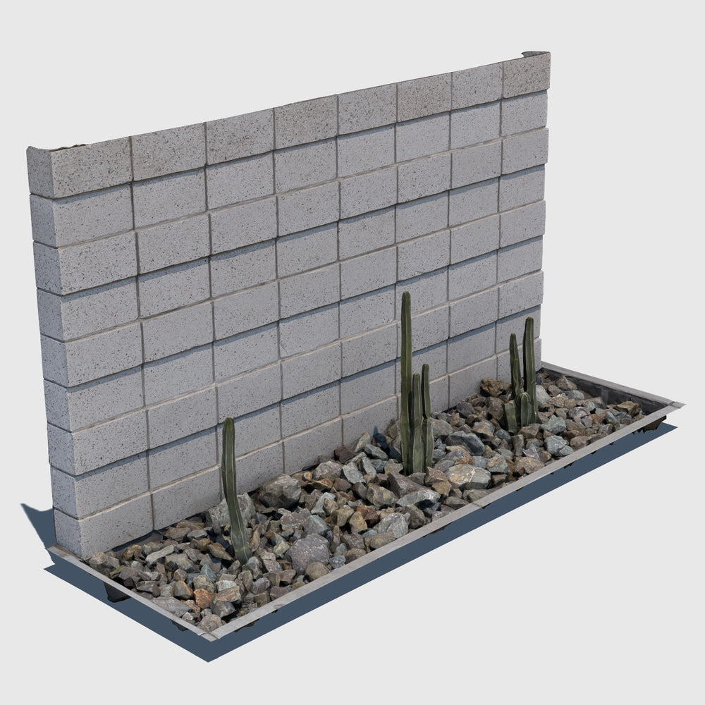 ground level planter full of medium sized rocks and 3 tall skinny cacti sections with a cement cinder block wall behind it rendered with low resolution texture