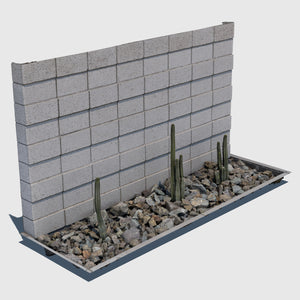 ground level planter full of medium sized rocks and 3 tall skinny cacti sections with a cement cinder block wall behind it rendered with medium resolution texture
