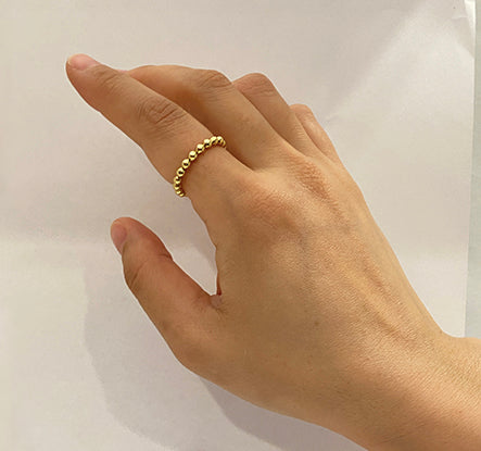 Gold Worry ring on pointer finger of hand on white background