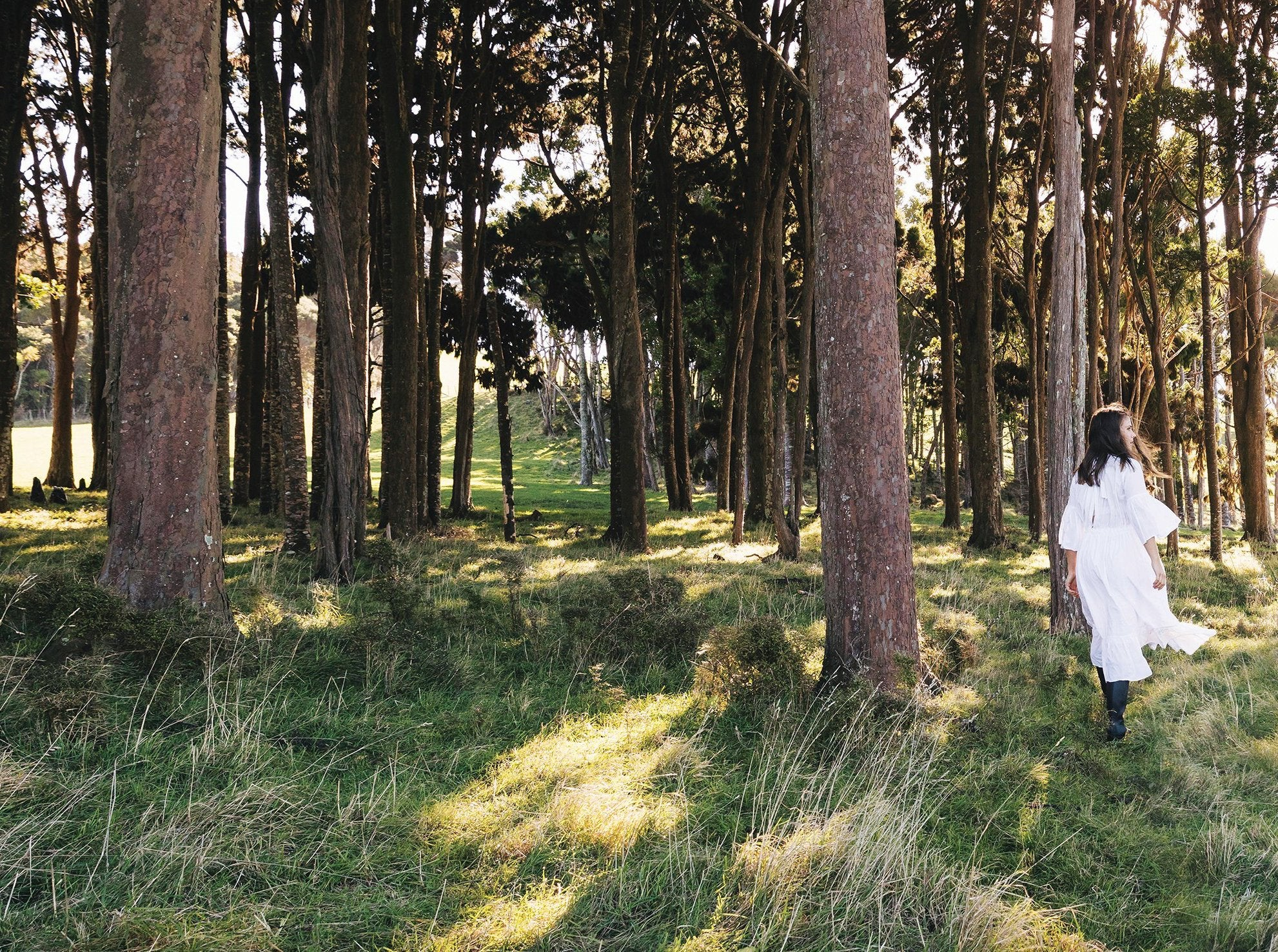 Woman in white dress walking in calm forest