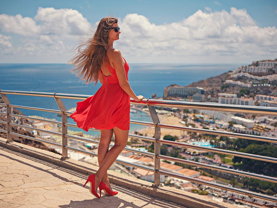 women in red dress looking at a seaside view