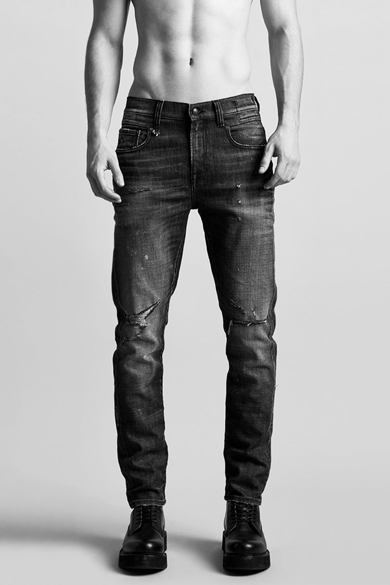 r13 Denim low rise jean with loose fit that tapers at the bottom in a dark wash with slight distressing at the knee