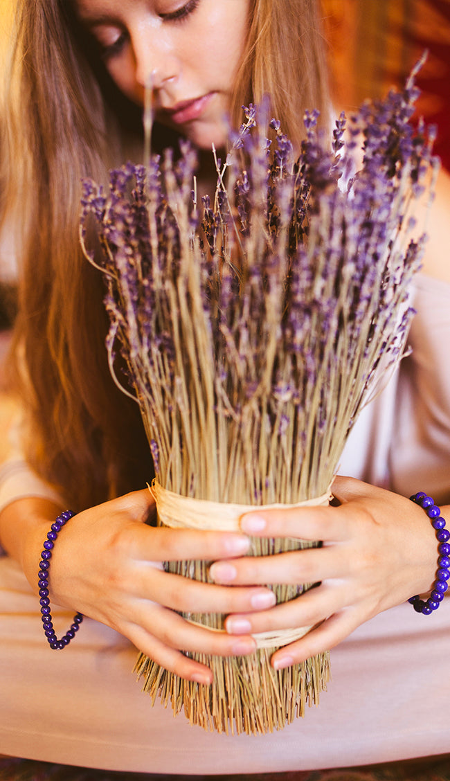 woman wearing lavender bracelet and arranging lavender plants