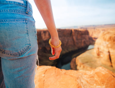 view of woman's hand wearing citrine bracelet with Horseshoe Bend , Arizona as background