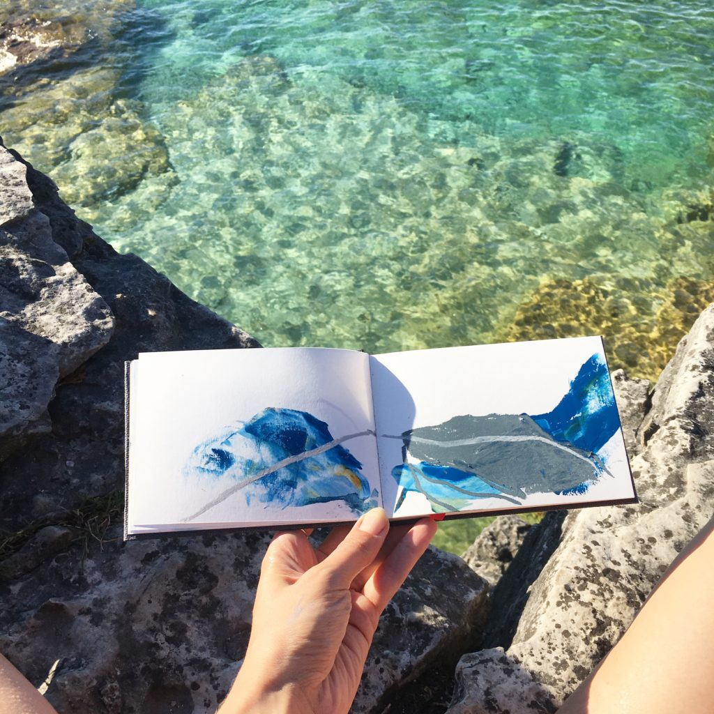 small sketchbook against clear blue water