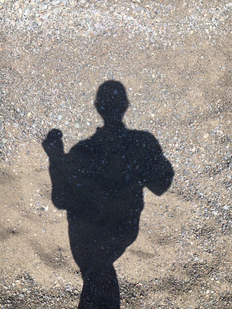 my shadow on sand holding a coffee