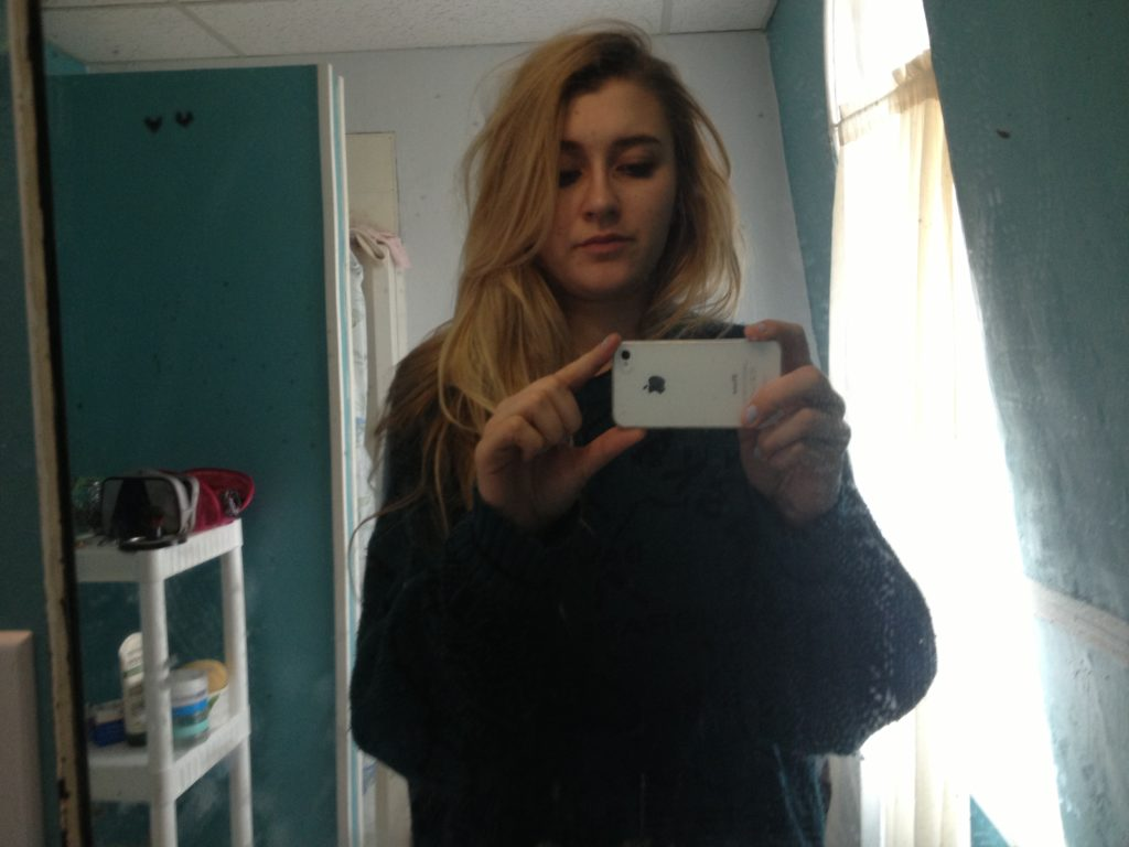 selfie in the mirror wearing a dark green sweater with bed head