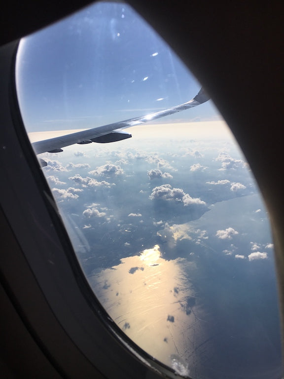 window view on an airplane with a clear sky and some fluffy white clouds